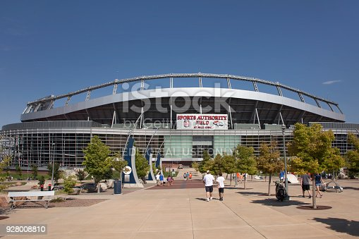 Visitors in shorts and t-shits walk towards the entrance of Sports Authority Field at Mile High to watch a free Broncos scrimmage game in the summertime in Denver.