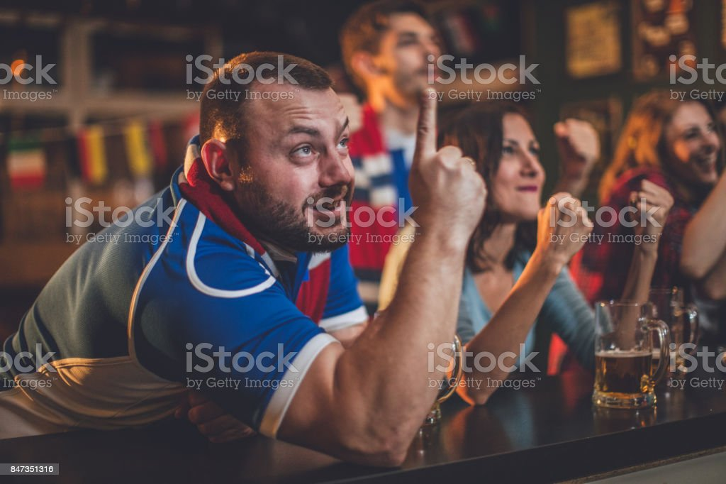Fans watching game at the bar stock photo