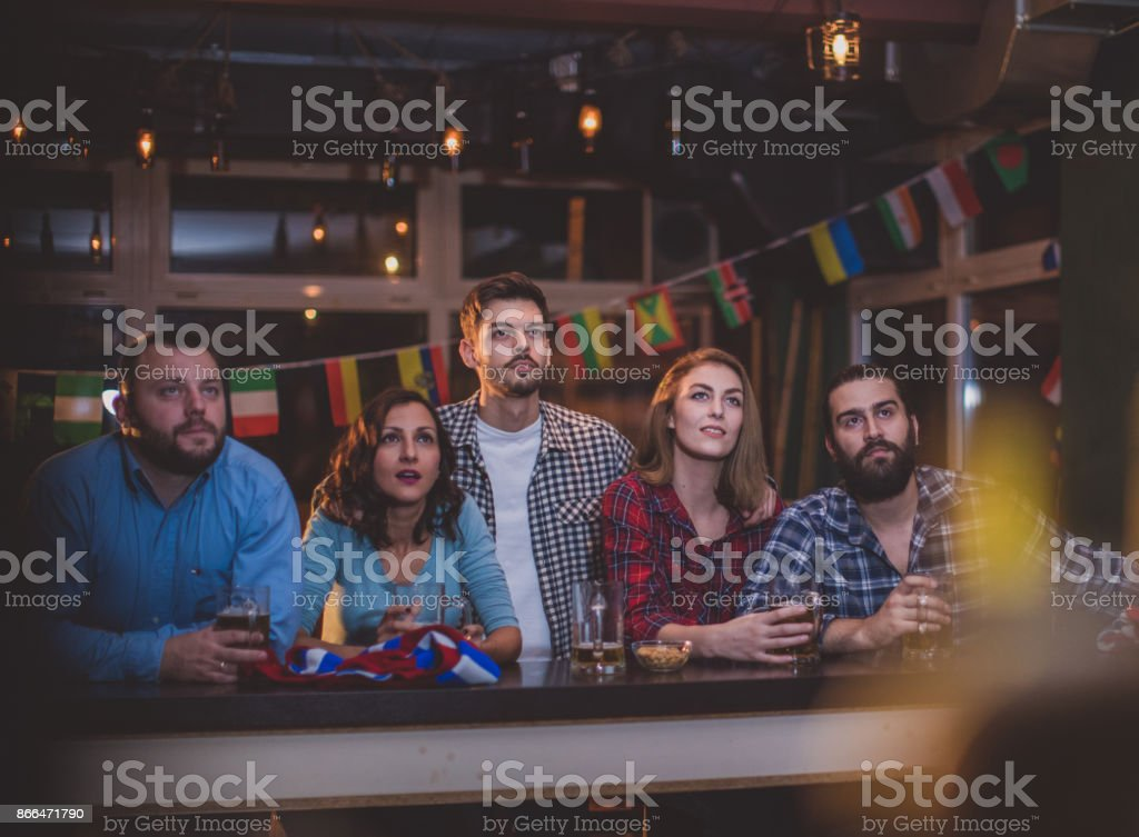 Fans watching game in pub stock photo