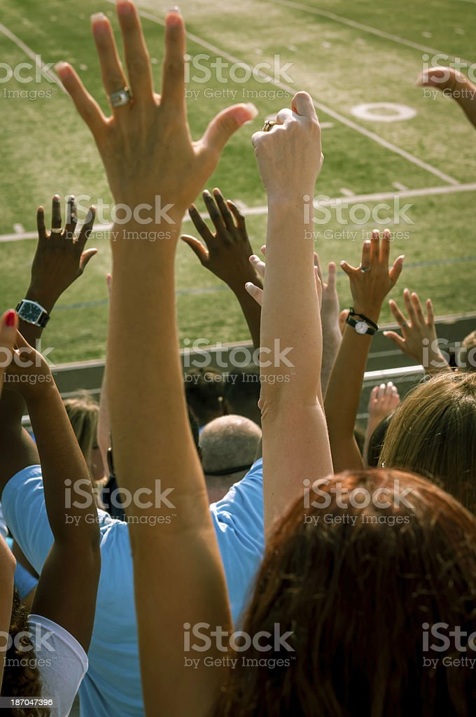 Fans with raised arms cheering for their team - III royalty-free stock photo