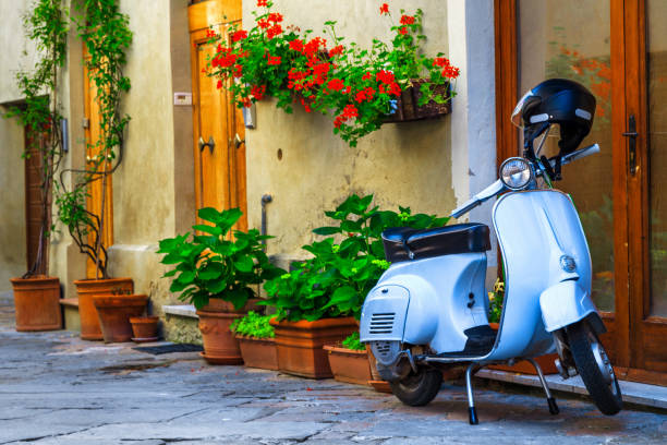 Fantastic Italian street with colorful flowers and scooter, Pienza, Tuscany stock photo