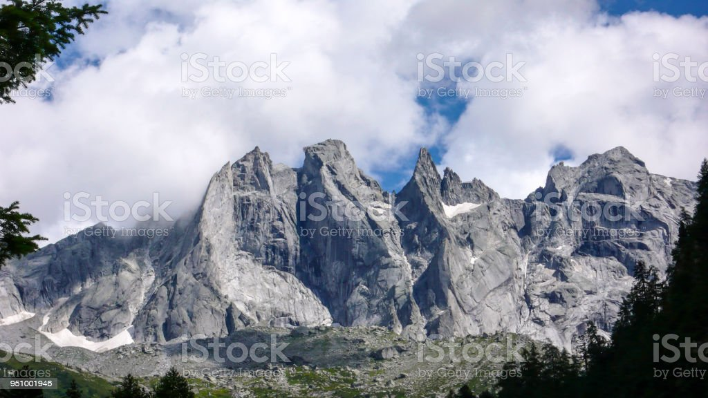 fantastic mountain landscape in the Swiss Alps with jagged sharp granite peaks under a cloudy sky stock photo