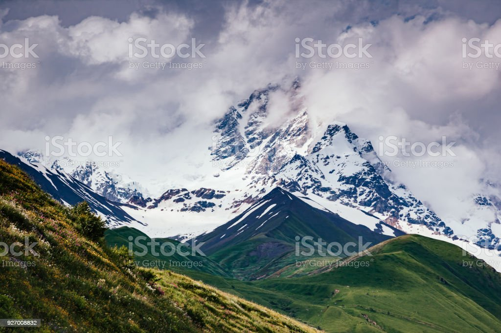 Fantastic range in mist at the foot Shkhara. Location place Svaneti, Mestia, Georgia, Europe. High Caucasus ridge. stock photo