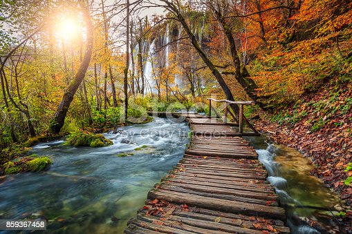 Majestic touristic wooden pathway in the colorful autumn deep forest with clean brook and spectacular waterfalls, Plitvice National Park, Croatia, Europe