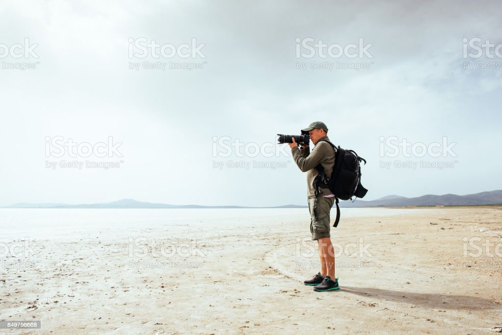 Fantastic views of Iceland. Gentle light color. Dramatic cumulus clouds. Local tourist takes pictures of landscapes. stock photo