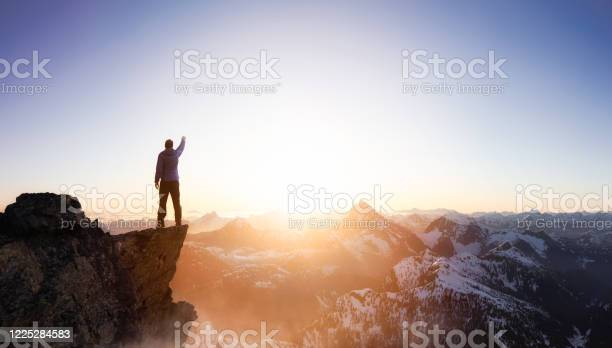 Photo of Fantasy Adventure Composite with a Man on top of a Mountain Cliff