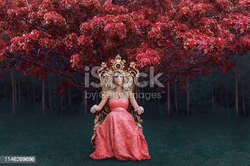 Fantasy concept of queen in luxury pink dress sitting on the throne in magical forest