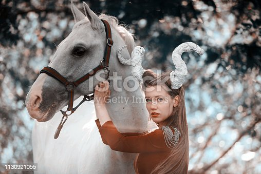 fantasy shot of devil woman with horns near her white horse posing in nature.