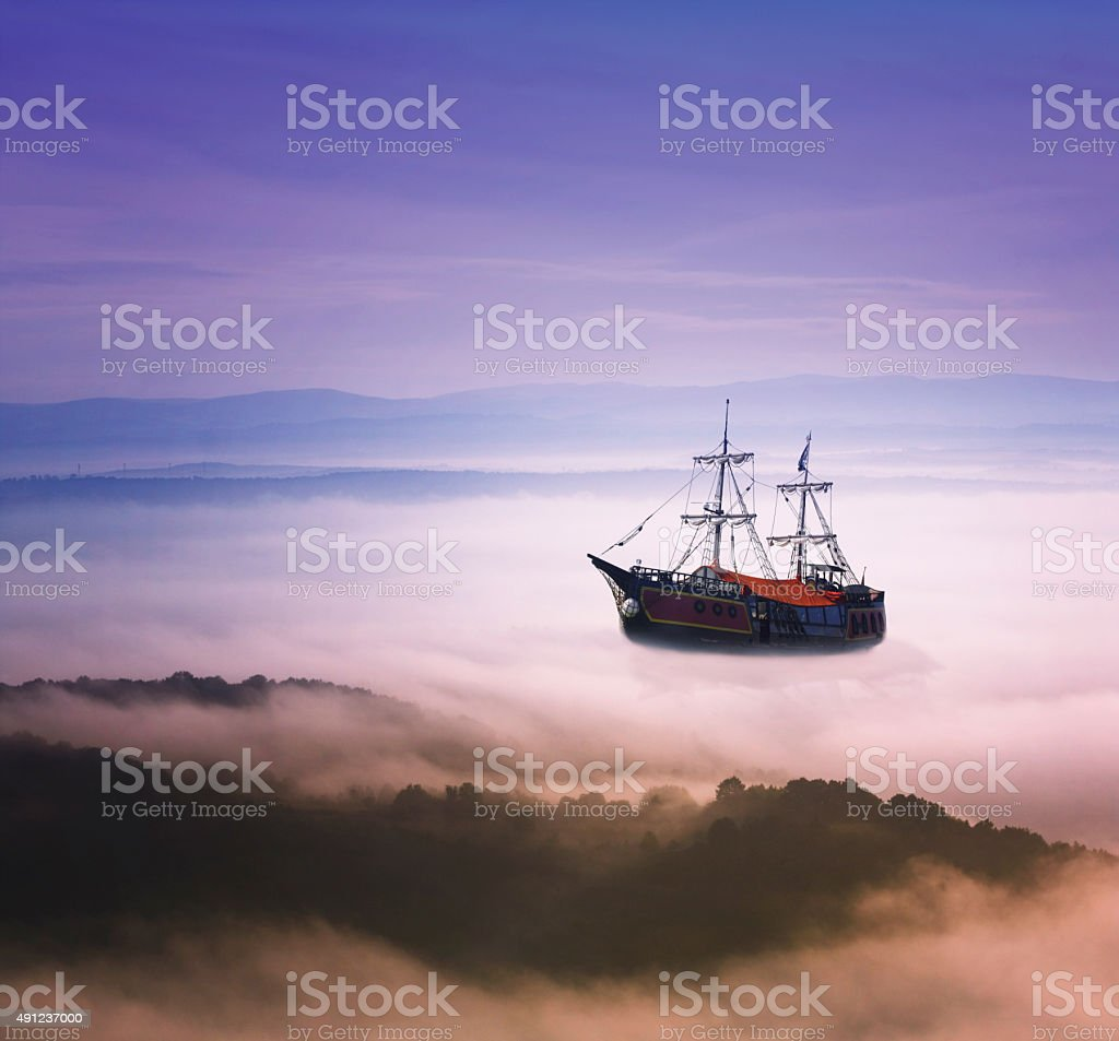 Fantasy masted ship  sailing over the clouds stock photo