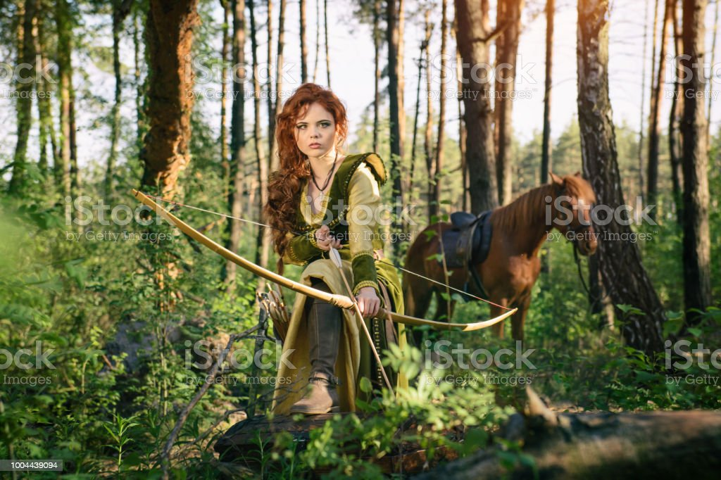 Fantasy medieval woman hunting in mystery forest stock photo