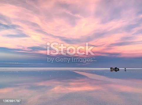 istock Fantasy pink sunset with magical clouds reflection in sparkling salt lake water 1282691797