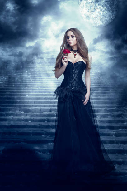 fantasy woman in black dress smelling rose flower, mystic girl in long gown - gothic kleid stock-fotos und bilder