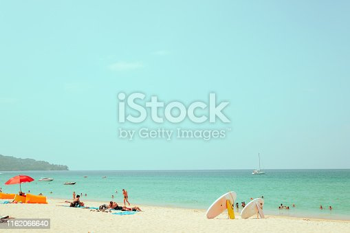 Far away image shot and blurred face of crowd people on sand beach with calm blue sea and sky background. summer vacation background concept. retro color tone.