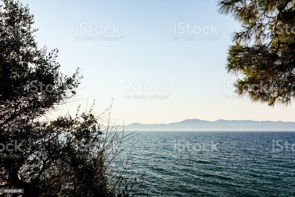 Far away Islands as silhouette across seashore stock photo