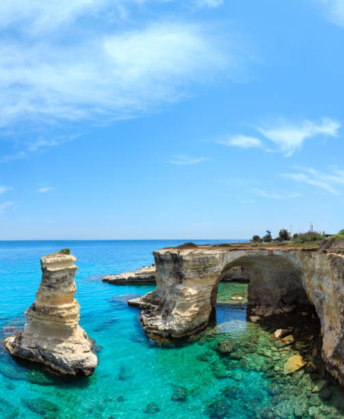Faraglioni at Torre Sant Andrea, Italy Picturesque seascape with cliffs, rocky arch and stacks (faraglioni), at Torre Sant Andrea, Salento sea coast, Puglia, Italy. People unrecognizable. rocky coastline stock pictures, royalty-free photos & images