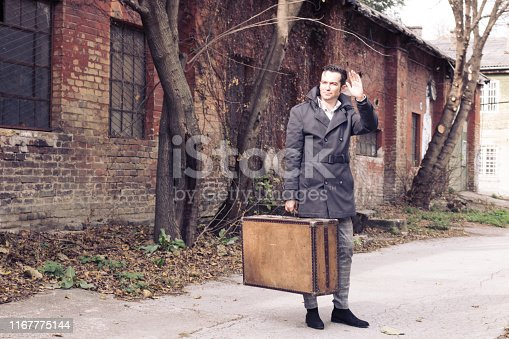 Stylish man with a suitcase and waving to someone while going away.