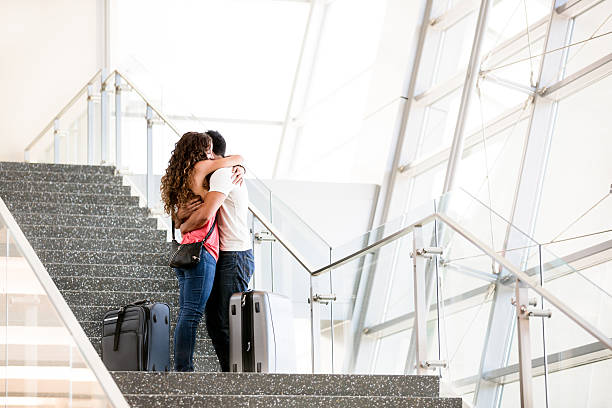 Farewell Couple embraced at an airport. They are sad to let each other go. long distance relationship stock pictures, royalty-free photos & images