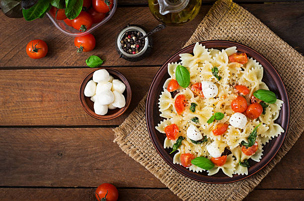 Farfalle Pasta - Caprese salad with tomato, mozzarella and basil. Farfalle Pasta - Caprese salad with tomato, mozzarella and basil. Top view bow tie pasta stock pictures, royalty-free photos & images