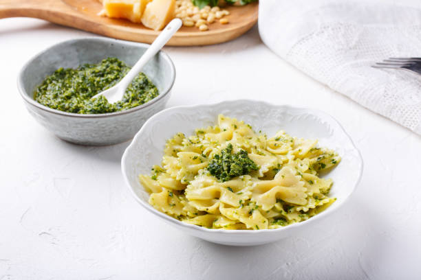 Farfalle pasta in  basil pesto sauce in white plate on white table. Farfalle pasta in  basil pesto sauce in white plate on white table. bow tie pasta stock pictures, royalty-free photos & images