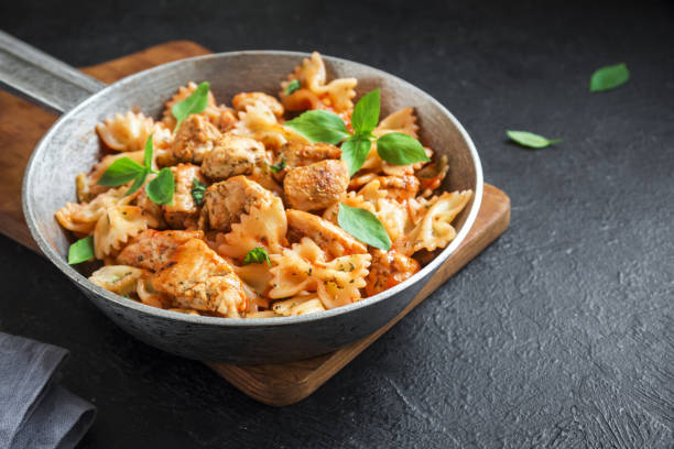 Farfalle pasta with chicken Farfalle pasta in tomato sauce with chicken,  basil in pan. Chicken italian bow tie pasta over concrete background with copy space, homemade italian food. bow tie pasta stock pictures, royalty-free photos & images