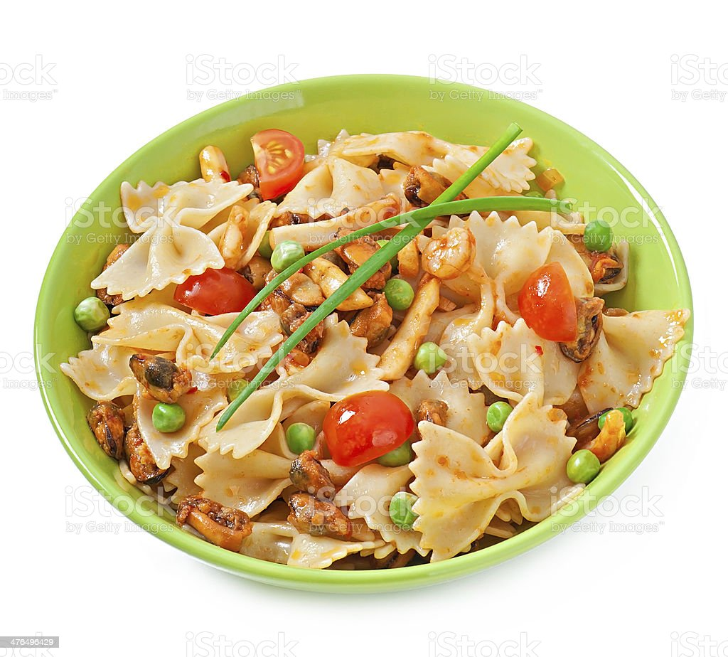 Farfalle pasta with seafood, cherry tomatoes and green peas stock photo