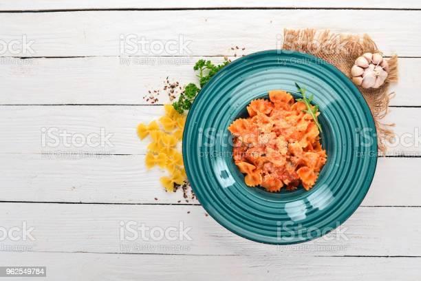 Foto de Massa Farfalle Com Tomate E Queijo Parmesão Sobre Um Fundo De Madeira Cozinha Italiana Vista Superior Copie O Espaço e mais fotos de stock de Almoço