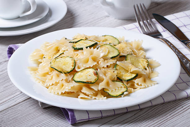 farfalle pasta with zucchini and cheese on a white plate farfalle pasta with zucchini and cheese on a white plate on the table. horizontal bow tie pasta stock pictures, royalty-free photos & images