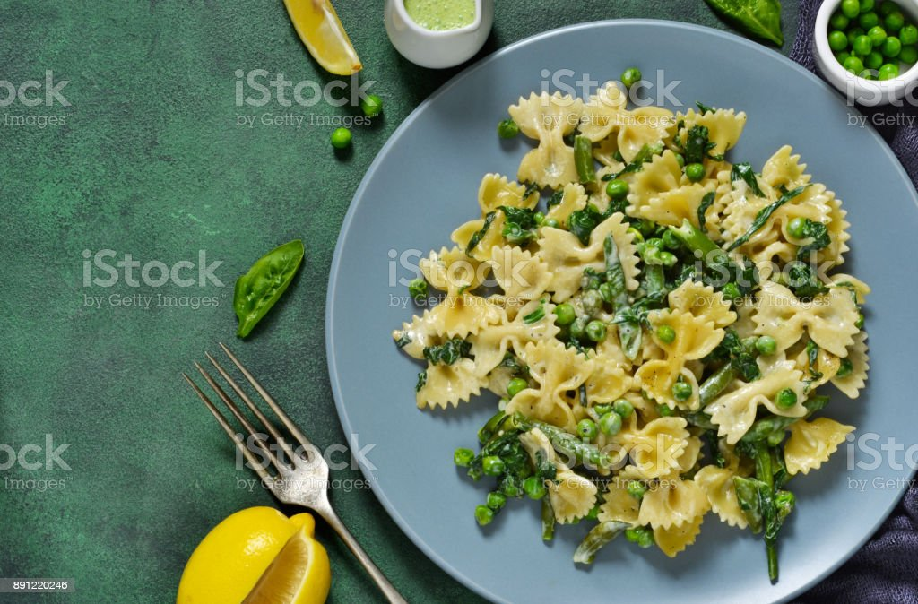 Farfalle with asparagus sauce, green peas and spinach green background. Homemade dinner. stock photo