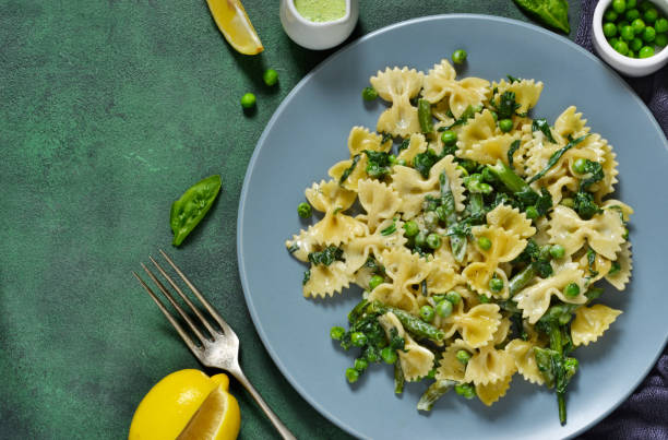 Farfalle with asparagus sauce, green peas and spinach green background. Homemade dinner. Farfalle with asparagus sauce, green peas and spinach green background. Homemade dinner. bow tie pasta stock pictures, royalty-free photos & images