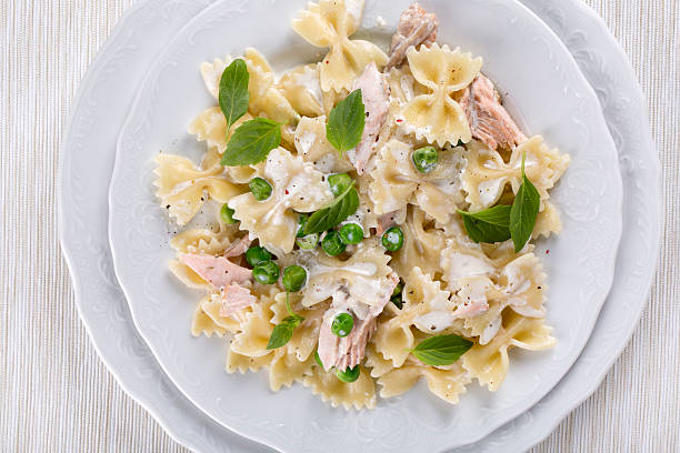 Farfalle with salmon Pasta. Farfalle with salmon, and green peas in a cream sauce. Top view. bow tie pasta stock pictures, royalty-free photos & images