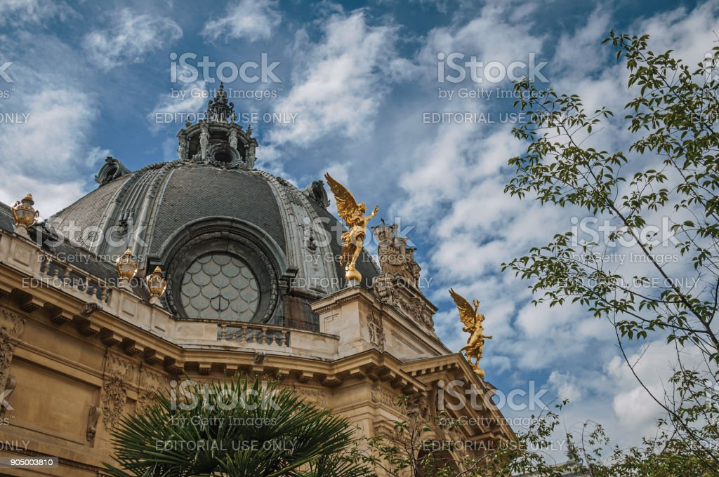 Far-fetched decoration of dome and golden statues on Petit Palais building top in Paris. stock photo