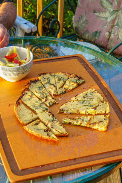 Farinata for breakfast Chickpea pancake or farinata for breakfast on a sun drenched outdoor table farinata stock pictures, royalty-free photos & images