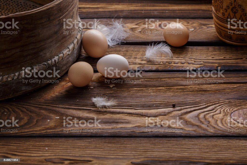 Farm fresh organic chicken eggs and feathers on rustic wooden background. Easter. stock photo