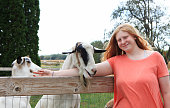 Caucasian farm girl loves her goats. Rural scene. Could be farm scene or petting zoo