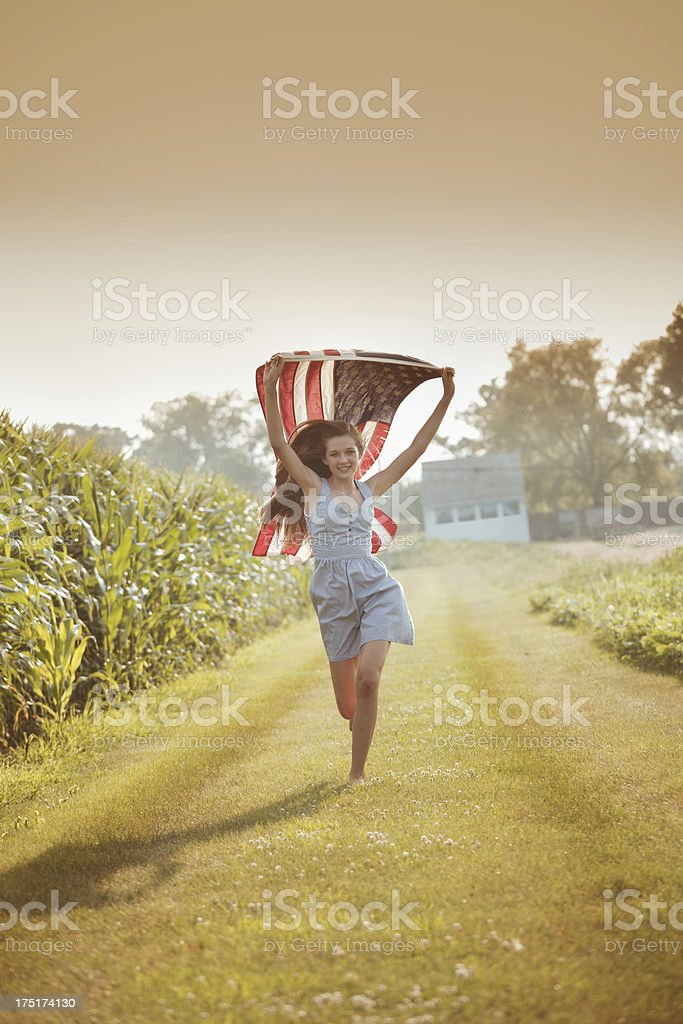 Farm Girl Running in Field with U.S. Flag royalty-free stock photo