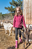 Farm Girl with Goat and Donkey on Sunny Spring Day