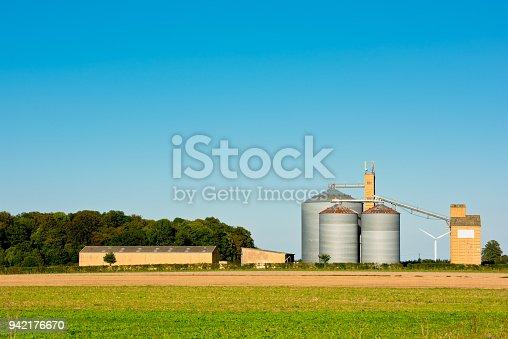 Farm grain silos in a field. Agriculture landscape