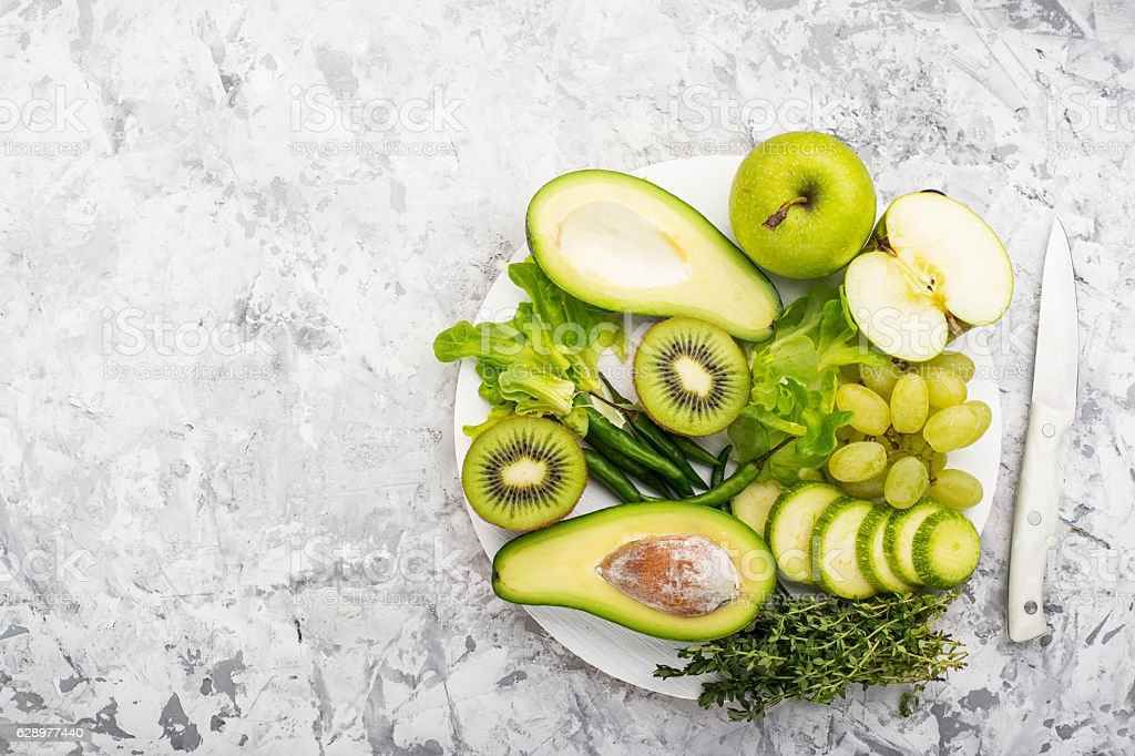 Farm green vegetables on gray marble background. Top view. Space stock photo