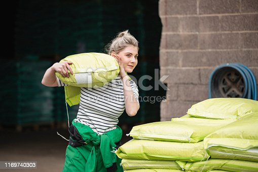 A front-view shot of a young caucasian female farmer, she is carrying a large sack over her shoulder.