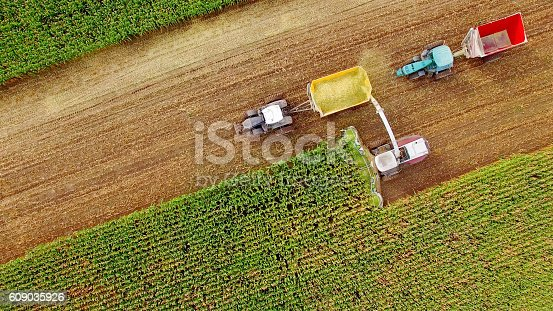 istock Farm machines harvesting corn in September, aerial view 609035926