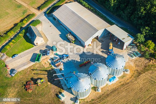 Aerial photo of modern farm, tractors, harvesters and agricultural equipment, barns and grain silos. ProPhoto RGB profile for maximum color fidelity and gamut.