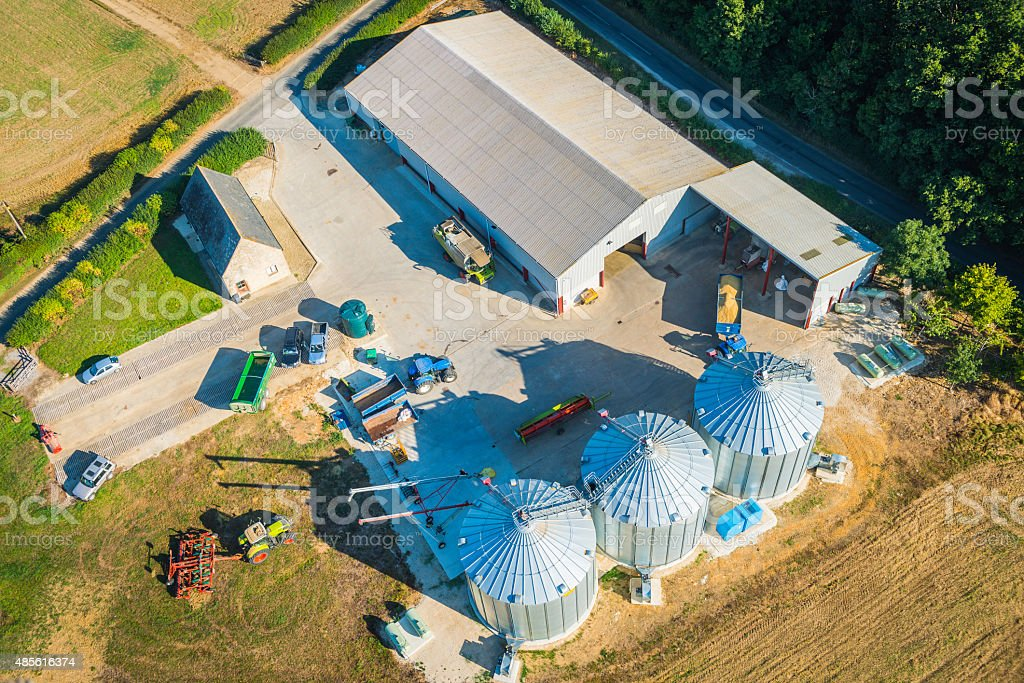 Farm outbuildings barns silos tractors agricultural machinery aerial view stock photo