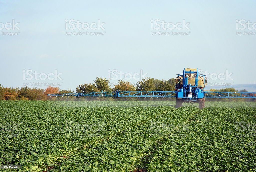 A farm sprayer distributes liquid chemicals to the crops  stock photo