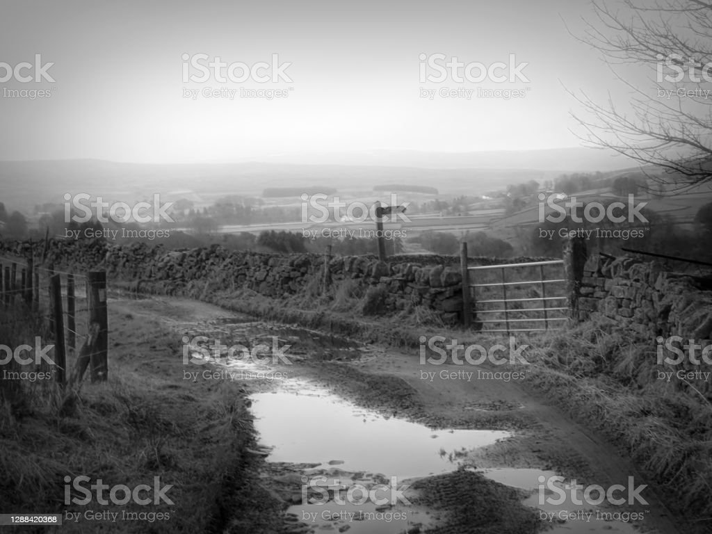 Farm track with pot holes in Alston, Cumbria. Farm track with pot holes in Alston, Cumbria. 2020 Stock Photo