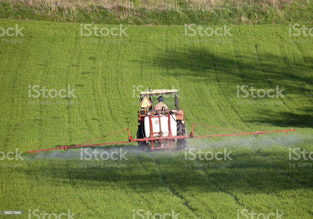 Farm tractor spraying field before planting royalty-free stock photo