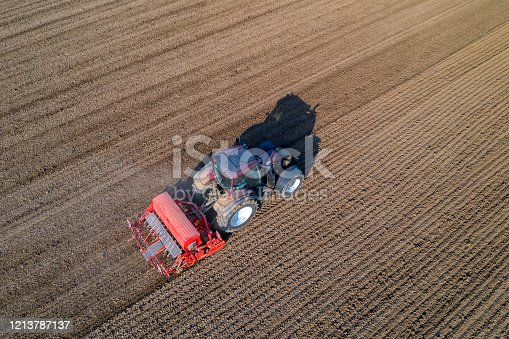 Aerial view of a farm tractor with seed drill sowing ploughed field in spring.