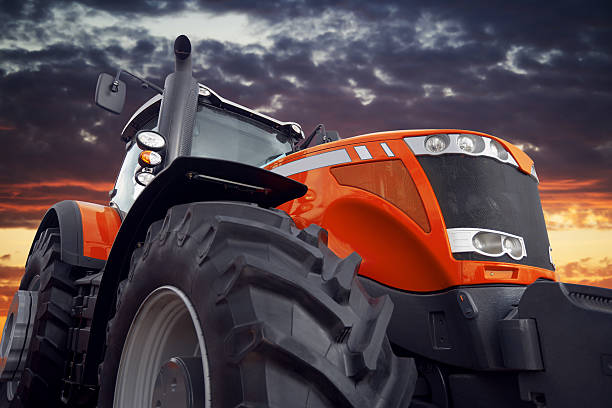 Farm tractor working at sunset stock photo