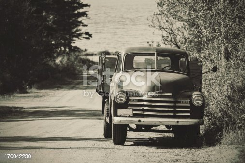 A late 1940's farm truck on a narrow country road near the Bay of Fundy.  Toned black and white.