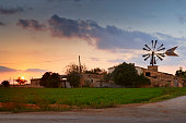 Farm with traditional wind wheel at sunset. Dirt road and field in foreground. Near Palma, Majorca, Spain, Europe.