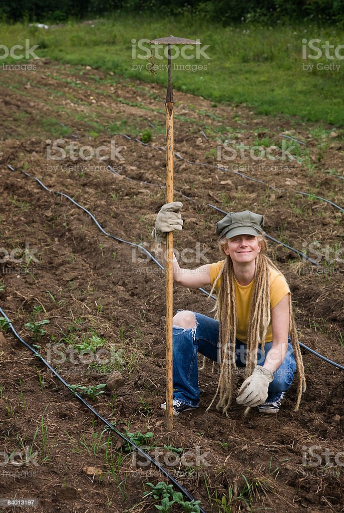 Farm worker holding hoe in field, portrait royalty-free stock photo